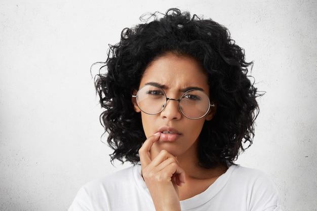 Ernstige aantrekkelijke jonge europese vrouw met een donkere huidskleur, gekleed in een wit casual t-shirt en een ronde bril, houdt de vinger op haar lippen, heeft een doordachte besluiteloze blik en denkt aan iets belangrijks