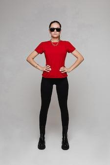Ernstige aantrekkelijke jonge vrouw die een rood t-shirt met zwarte broek en laarzen draagt. zonnebril op haar gezicht. mode concept