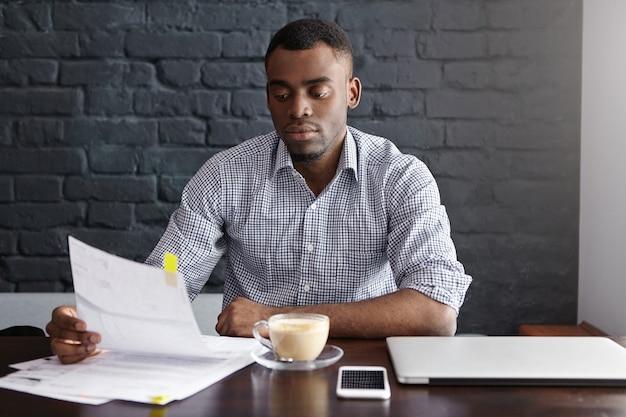Ernstige aantrekkelijke jonge zakenman die het geruite document van de overhemdslezing in zijn handen draagt