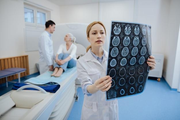 Ernstige aardige jonge oncoloog die het resultaat van de ct-scan vasthoudt en onderzoekt terwijl ze een diagnose stelt aan haar patiënt
