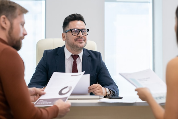 Ernstige advocaat of auditor die tijdens overleg naar jonge vrouw luistert