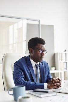 Ernstige afrikaanse mannelijke leider zit op zijn werkplek achter computer en werkt op kantoor