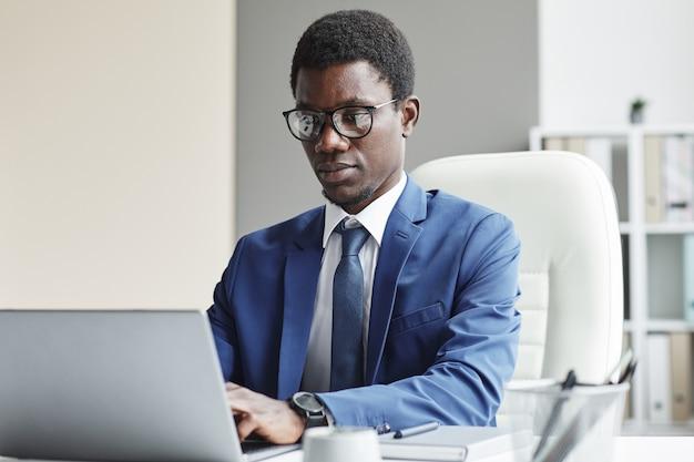 Ernstige afrikaanse zakenman in brillen die zich op zijn online werk concentreren die hij aan de lijst zit te typen op laptop op kantoor