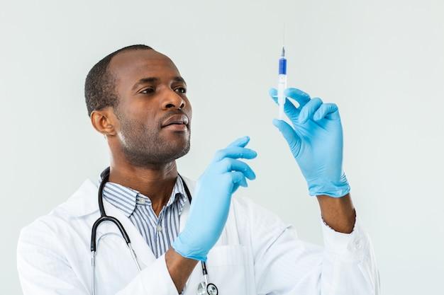 Ernstige afro-amerikaanse arts die een injectie geeft terwijl hij een spuit vasthoudt