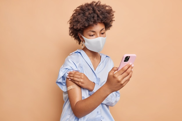 Ernstige afro-amerikaanse vrouw met krullend haar downloadt speciale applicatie op smartphone om online vaccinatiecertificaat te krijgen draagt wegwerp gezichtsmasker toont gepleisterde arm na vaccinatie