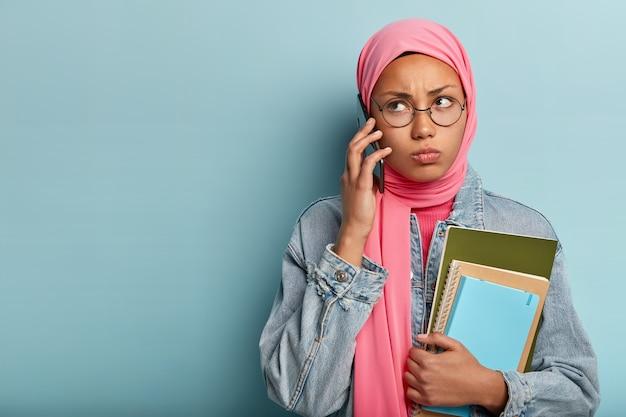 Ernstige arabische vrouw belt via de mobiele telefoon, kijkt opzij, heeft een norse gezichtsuitdrukking en draagt een ronde bril