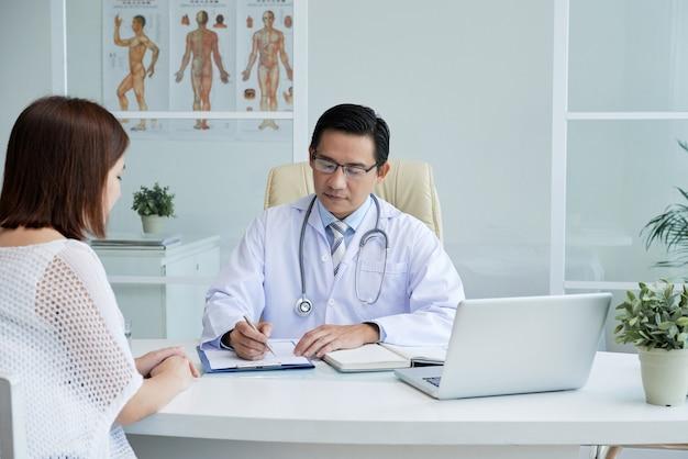 Ernstige arts die de medische geschiedenis van de patiënt controleert, naar haar klachten luistert en een diagnose stelt