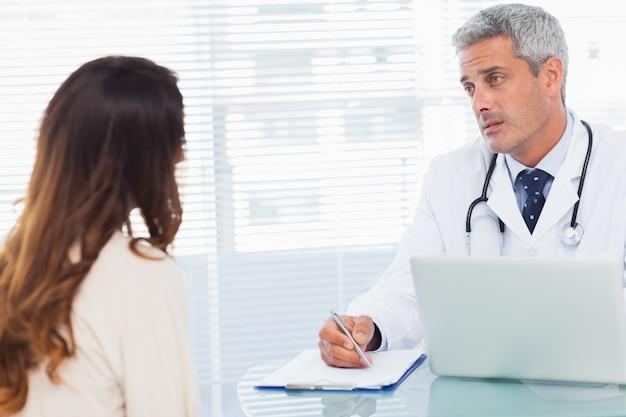 Ernstige arts die met zijn patiënt spreekt en op een notitieboekje schrijft