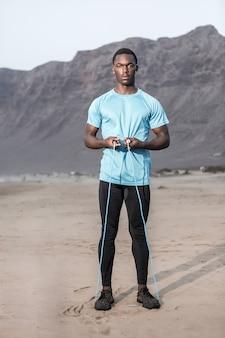Ernstige atleet met touwtjespringen op strand