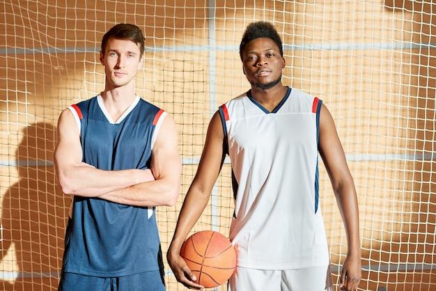 Ernstige atletische knappe basketbal concurrenten klaar voor spel