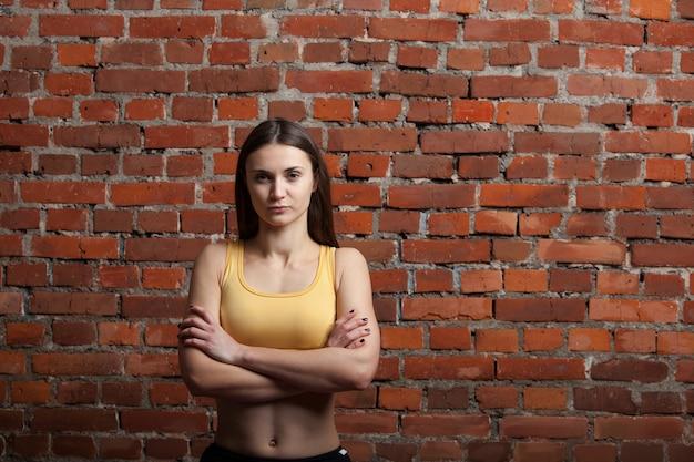 Ernstige atletische vrouw op bakstenen muurachtergrond