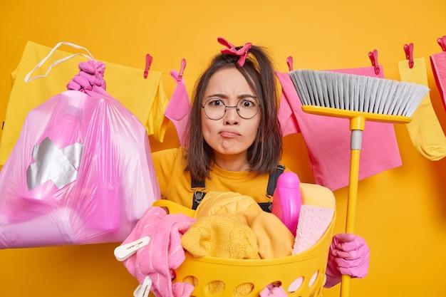 Ernstige attente aziatische vrouw kijkt verbaasd draagt vuilniszak en bezem doet de was thuis doet huishoudelijke taken draagt ronde bril geïsoleerd over gele achtergrond. huishoudconcept