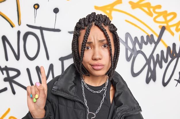 Ernstige attente vrouw punten hierboven heeft kleurrijke manicure en dreadlocks ontevreden gezichtsuitdrukking draagt zwarte jas met metail kettingen om de nek vormt tegen graffitimuur