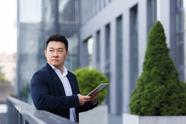 Ernstige aziatische baas leest nieuws van tablet in de buurt van moderne kantoor mannelijke zakenman in pak