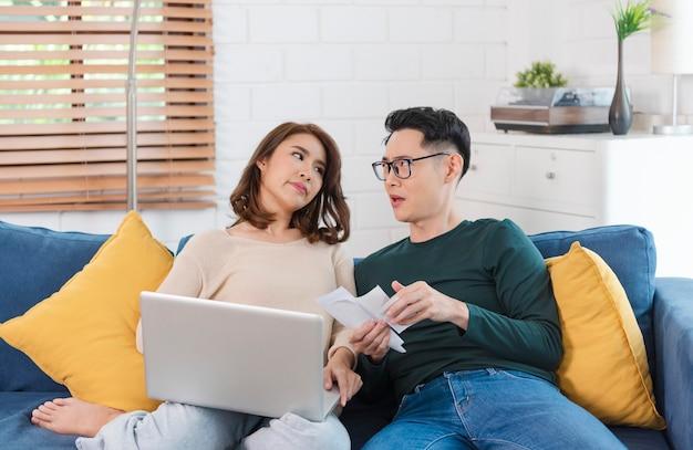 Ernstige aziatische echtgenoot die de rekeningen van nutsbedrijven analyseert die thuis bij elkaar zitten