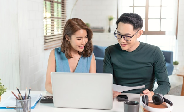 Ernstige aziatische echtgenoot die de rekeningen van nutsbedrijven analyseert die thuis samen zitten.