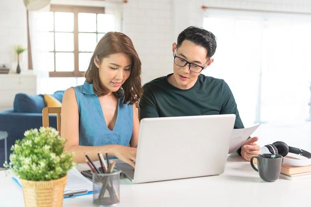 Ernstige aziatische man controleren analyse van de rekeningen van staatshulpmiddelen die thuis samen zitten.