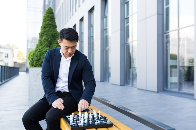 Ernstige aziatische man die buiten schaakt, zakenman die schaak denkt te zitten op een bankje in de buurt van het kantoorcentrum