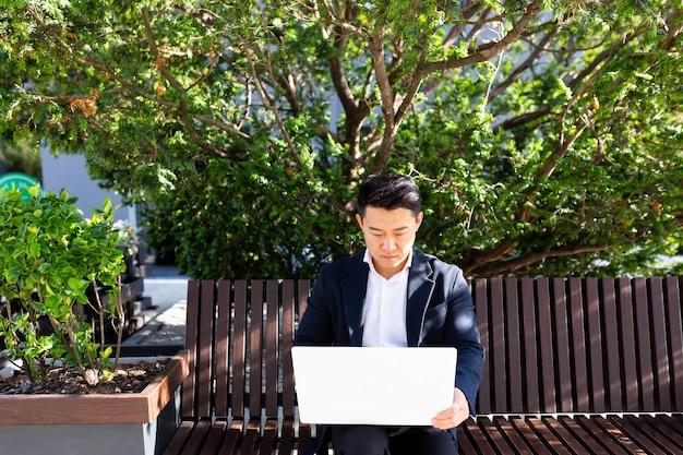 Ernstige aziatische man freelancer in pak werkt op laptop zittend op de bank gedurende de dag