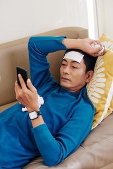 Ernstige aziatische man met griep die op bank rust en artikel op smartphonescherm leest
