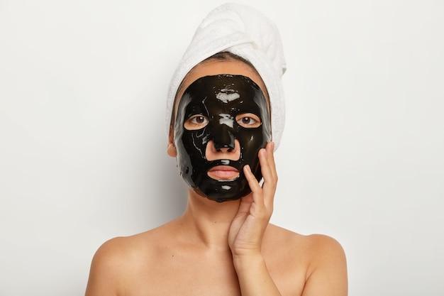 Ernstige aziatische vrouw heeft thuis cosmetische ingrepen, past een zwart zuiverend gezichtsmasker toe, ziet er recht uit, raakt zachtjes de wang aan, draagt een witte zachte handdoek op het hoofd
