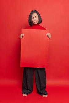 Ernstige aziatische vrouw houdt een rood reclamebord vast en raadt aan om uw informatie hier te plaatsen, een banner met een stijlvolle outfit vormt tegen een heldere studiomuur