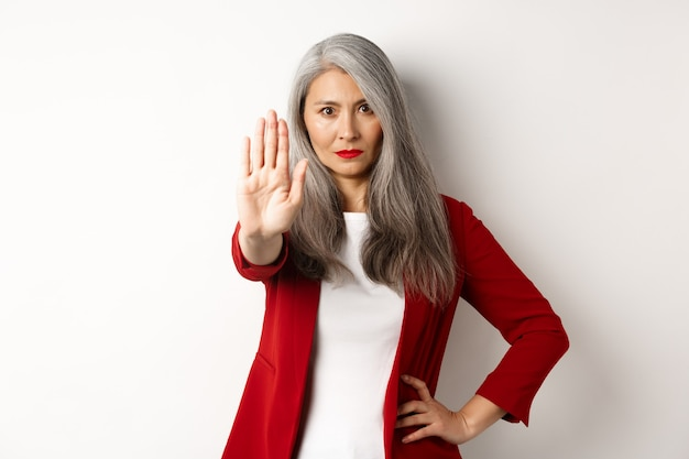 Ernstige aziatische vrouw in rode blazer die stopbord toont, nee zegt, fronsend en iets slechts verwerpt, staande tegen een witte achtergrond.