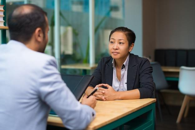 Ernstige aziatische vrouw ontmoeting met zakenpartner