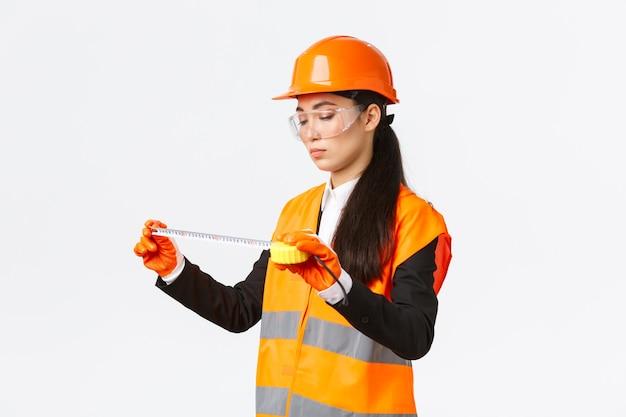 Ernstige aziatische vrouwelijke bouwingenieur, technicus inspecteert lay-out, meet iets, kijkt naar meetlint met gefocust gezicht, staande op witte achtergrond in veiligheidsuniform