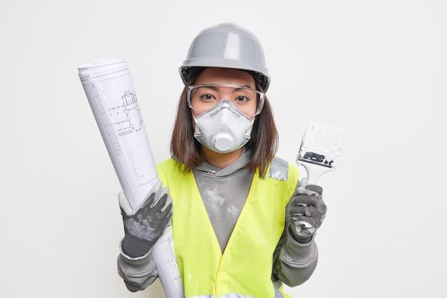 Ernstige aziatische vrouwelijke ingenieur draagt een bouwuniform met tekeningen en een verfkwast ontwikkelt een architectonisch project voor het bouwen van een nieuw hotel maakt gebruik van veiligheidsuitrusting