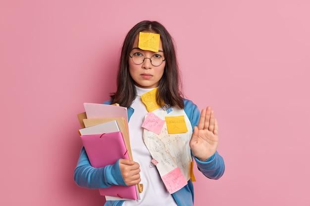 Ernstige aziatische vrouwelijke student stopt gebaar houdt palm naar voren in stopgebaar