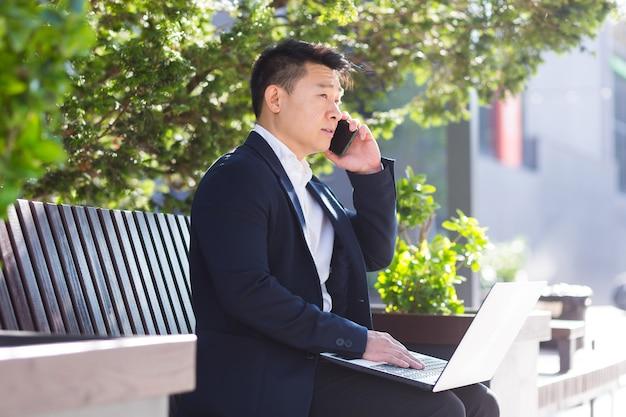 Ernstige aziatische zakenman die aan een laptop werkt en aan de telefoon praat terwijl hij op een parkbank in de buurt van het kantoor zit tijdens de lunchpauze