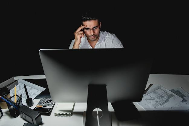 Ernstige aziatische zakenman die laat bij nacht in het bureau werkt