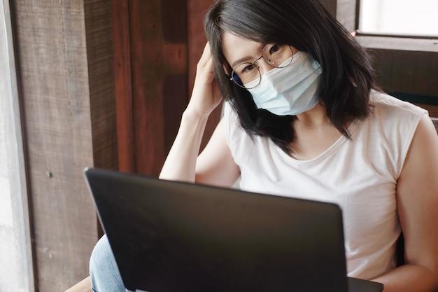 Ernstige aziatische zakenvrouw draagt een masker voor civid-19 en online werken met laptop. ze zoekt sociaal op internet in een coffeeshop. gezond en zakelijk met technologieconcept
