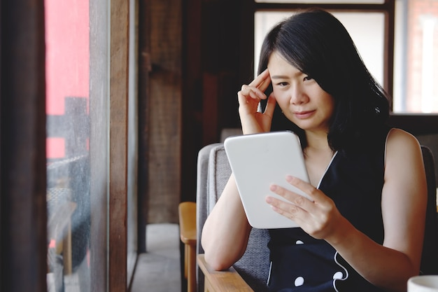 Ernstige aziatische zakenvrouw leest en heeft hoofdpijn met online nieuws op tablet op modern kantoor. gezond en technologisch concept.