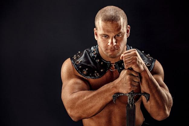 Ernstige barbaar in leren kostuum met zwaard. portret van balded gespierde gladiator.