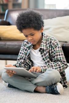 Ernstige basisschooljongen van afrikaanse etniciteit die bij een zwarte leren bank op de vloer in de woonkamer zit en online educatieve video's bekijkt