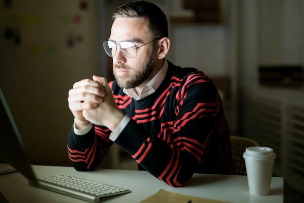 Ernstige beambte die met computer in donker bureau werkt