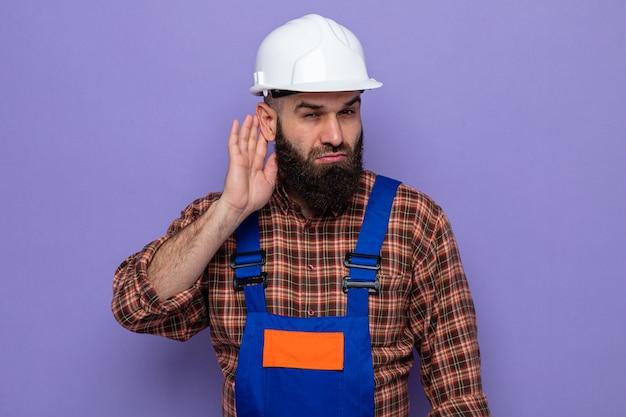 Ernstige bebaarde bouwman in bouwuniform en veiligheidshelm die probeert te luisteren terwijl hij zijn hand bij zijn oor houdt