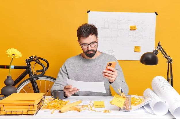 Ernstige bebaarde europese man geconcentreerd op papier gebruikt mobiele telefoon, maakt tekeningen voor bouwbedrijf omringd met blauwdrukrollen, stickers en papieren. baanconcept.