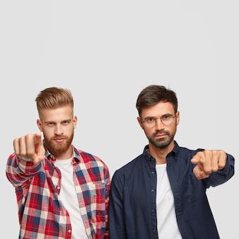 Ernstige bebaarde gemberman en zijn broer wijzen met wijsvingers direct op camera