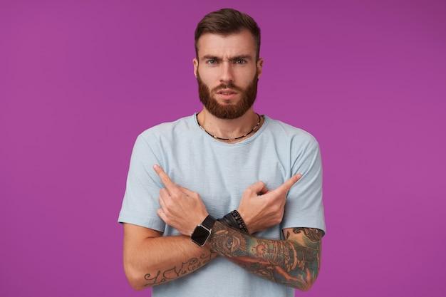 Ernstige bebaarde getatoeëerde brunette man met trendy kapsel gekruiste armen op zijn borst en wijsvingers serieus tonen en lippen vouwen, geïsoleerd op paars