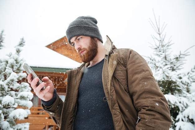 Ernstige bebaarde jongeman die smartphone gebruikt die in de winter buiten staat