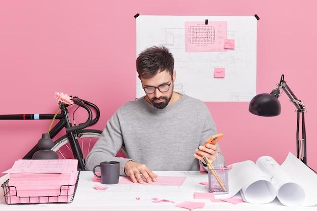 Ernstige bebaarde man controleert informatie in papieren houdt mobiele telefoon vast en bereidt architectonisch project nonchalant gekleed in coworking-ruimte