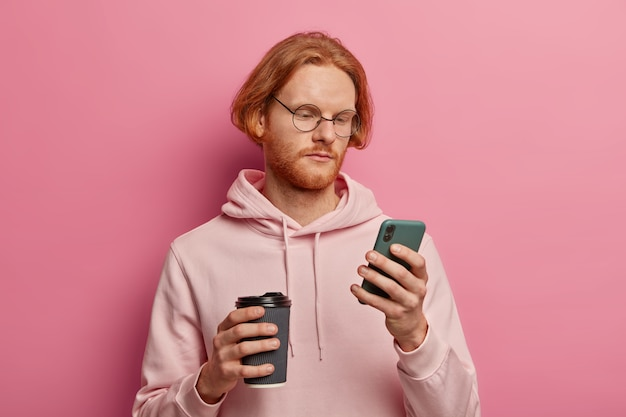 Ernstige bebaarde man gebruikt moderne mobiele telefoon voor online communicatie, controleert e-mails, geconcentreerd op het scherm, drinkt afhaalkoffie, draagt een optische bril en hoodie, geïsoleerd op roze muur