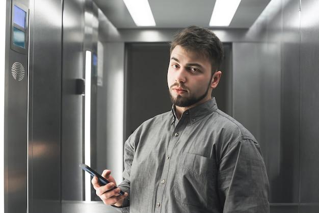 Ernstige bebaarde man in een shirt staat in de lift met een smartphone in zijn hand