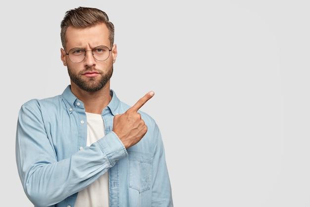 Ernstige bebaarde man met een strikte uitdrukking, trekt ergens je aandacht naar, gekleed in een blauw shirt, wijst richting ergens