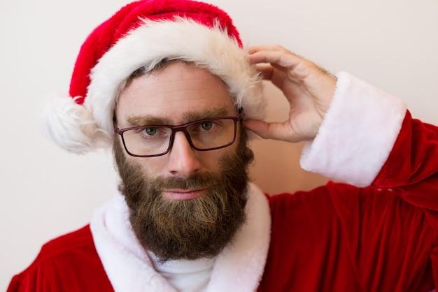 Ernstige bebaarde man met kerstman kostuum en bril