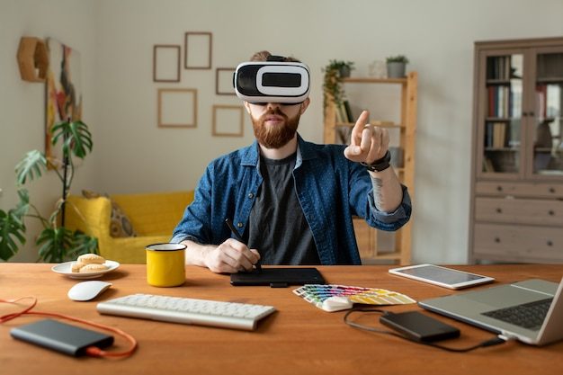Ernstige bebaarde ontwerper zittend aan tafel en puttend uit digitizer tijdens het gebruik van virtual reality simulator thuis