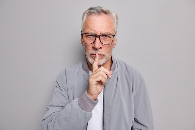 Ernstige bebaarde oudere man maakt stiltegebaar en drukt wijsvinger tegen lippen